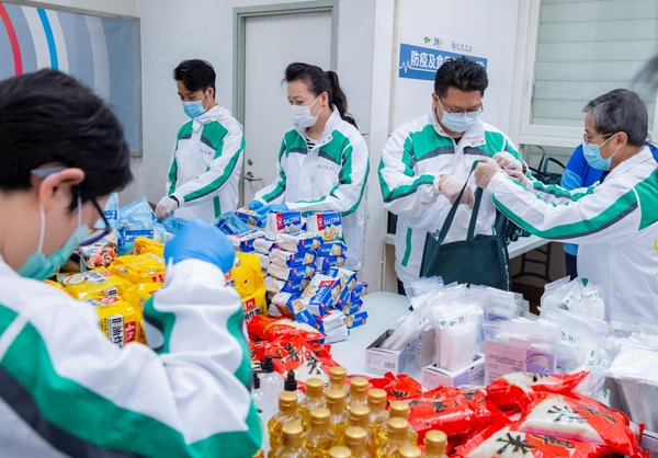 Volunteers from the Hang Lung As One Volunteer Team help package the health and food kits